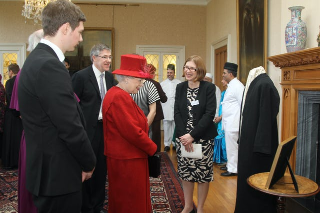 Her Majesty Queen Elizabeth II is met by a delegation of British Baha'is at a special multifaith gathering to mark her Diamond Jubilee. Invited to display a treasured object from their faith, the Baha'i community exhibited a robe of 'Abdu'l-Baha and a framed calligraphic rendering of words from His first ever public speech, given in London in 1911.