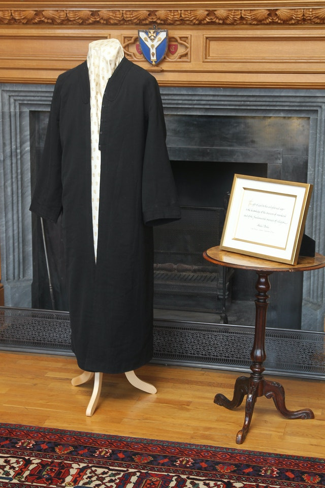 """A robe worn by 'Abdu'l-Baha and a framed calligraphic rendering of words from His first ever public speech, delivered on 10 September 1911 at London's City Temple: """"The gift of God to this enlightened age is the knowledge of the oneness of mankind and of the fundamental oneness of religion."""" The historic items were exhibited at a reception held at Lambeth Palace to mark the Diamond Jubilee of Her Majesty Queen Elizabeth II."""