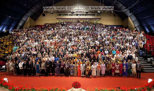 A group photograph of the 11th International Baha'i Convention. The bouquet of red roses in the foreground noted the absence of delegates from Iran.
