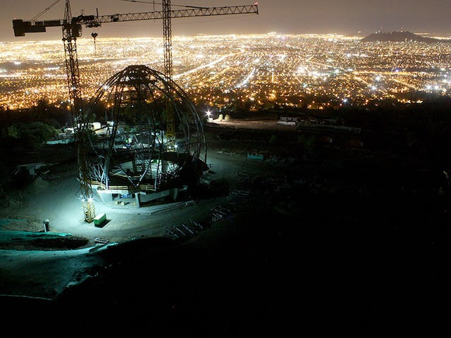 A view of the House of Worship superstructure at night, overlooking the city of Santiago.