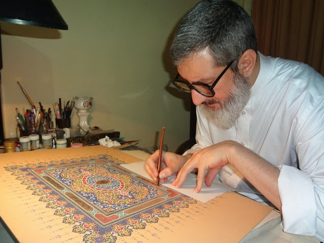 Ayatollah Abdol-Hamid Masoumi-Tehrani perfecting an illuminated work of calligraphy. The words used in this piece are from the writings of Baha'u'llah.