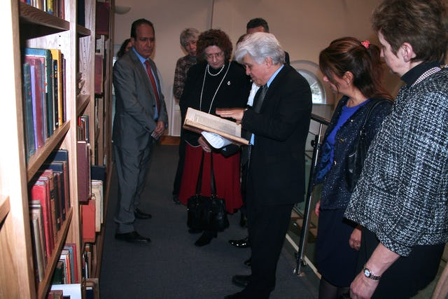Dr. Moojan Momen shows a rare Persian-language manuscript to guests gathered at the official opening of the Afnan Library in Sandy, U.K., on 12 February 2015.