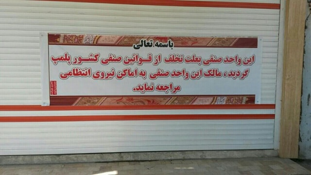 """A banner placed on the front of one of some 79 Baha'i-owned businesses which were closed on the morning of 25 October 2014 in a systematic state-sponsored attack on the Baha'i community in one of the regions of Iran. It reads: """"This commercial unit has been sealed owing to violation of trading laws/rules. The owner of this commercial unit should report to the police."""""""