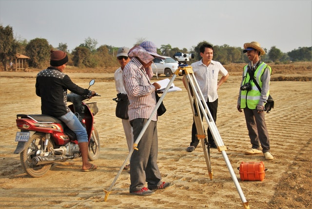 A team investigates the road levels at the site designated for the Baha'i House of Worship in Battambang, Cambodia.