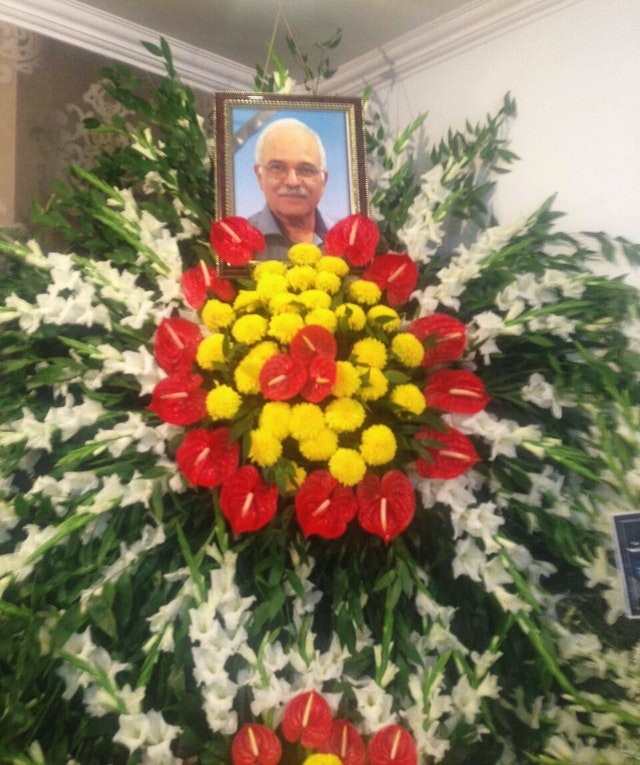 A photograph of Farhang Amiri placed atop a floral bouquet at his funeral