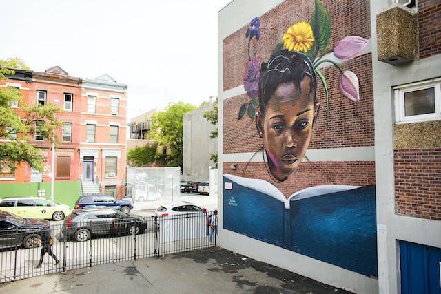 """The mural """"To Blossom"""" by artist Tatyana Fazalizadeh is located at PS92 in Harlem. It is a part of the Education is Not a Crime campaign, which raises awareness about the denial of education to Iranian Baha'i."""