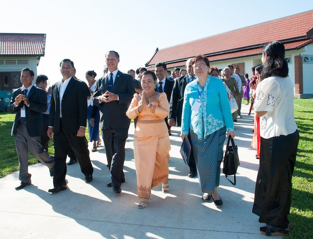 Representative of the Universal House of Justice, Ms. Sokuntheary Reth (center), walks with government representatives and representatives of the Baha'i community.