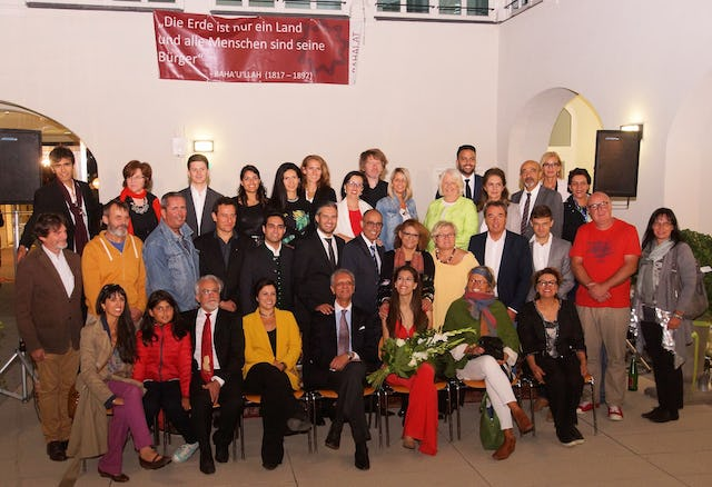 Mayor Richard Hemmer (second row, fourth from the right) and members of the city council, together with some of the volunteers at the celebration to commemorate the bicentenary of the birth of Baha'u'llah in Bruck, Austria, last week