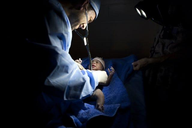 A volunteer doctor examines Tina Rose Wome shortly after her birth at a Baha'i school in Port-au-Prince. A medical team from Canada and the United States had set up a makeshift clinic at the school, and all 18 team members were on hand for the arrival of the baby, named after Dr. Tina Edraki and Rose Cabot, the doctor and nurse who delivered her. (Baha'i World News Service photographs)