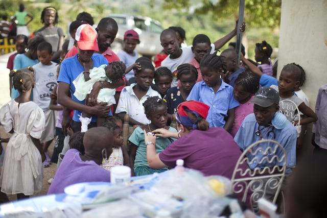 Dr. Munirih Tahzib, a pediatrician from Hoboken, New Jersey, treats a child next to a collapsed school in a village outside of Port-au-Prince. At a separate stop at an orphanage, Dr. Tahzib and other volunteers examined 150 children in need of medical attention.