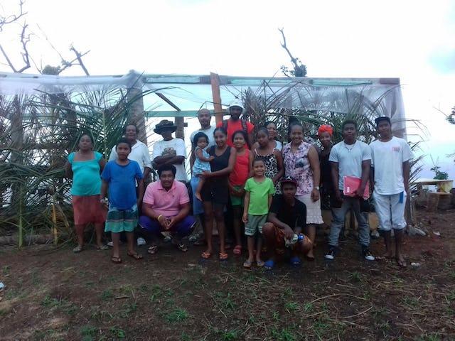 Amigos y vecinos se reúnen frente a un invernadero que construyeron juntos. La comunidad de esta parte del remoto territorio de Kalinago ha comenzado a llevar a cabo clases para niños y jóvenes adolescentes en el lugar, así como reuniones de oraciones abiertas a todos.