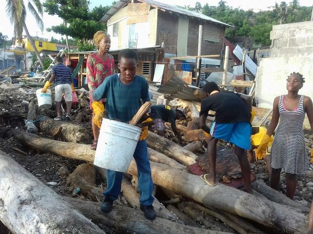 Vecinos del barrio de Newtown en Roseau ayudan a limpiar la bahía de escombros después de la destrucción dejada por el huracán.