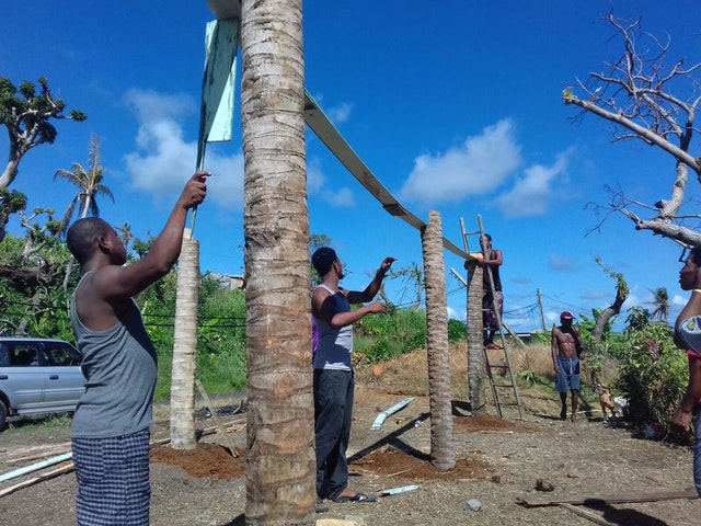 Youth and adults work together to build a greenhouse in the Kalinago territory.