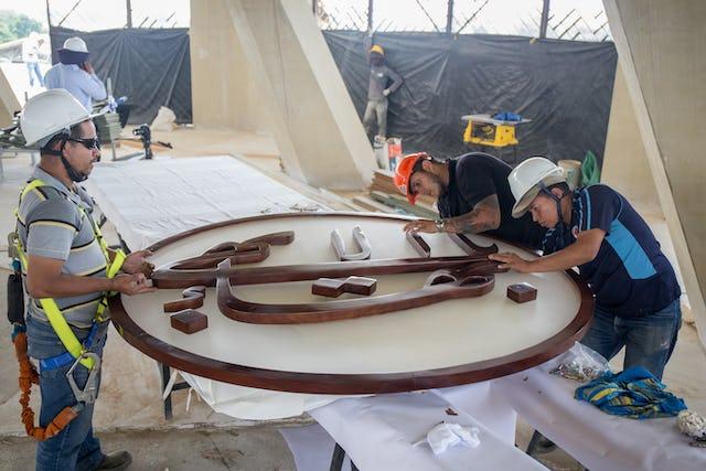 Les charpentiers de la firme qui a sculpté le symbole du « Plus-Grand-Nom » se préparent à l'élever au pinacle du dôme de la maison d'adoration locale d'Agua Azul, en Colombie.