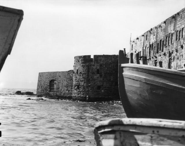Bahá'u'lláh est entré dans Acre le 31 août 1868 par la porte de la mer, visible à gauche le long de la digue. Cette photo, datant de 1920, montre à quoi ressemblait la porte de la mer à l'arrivée de Bahá'u'lláh, avec l'eau léchant le pied du mur. Aujourd'hui, cette zone le long de l'ancienne digue est une promenade pavée.