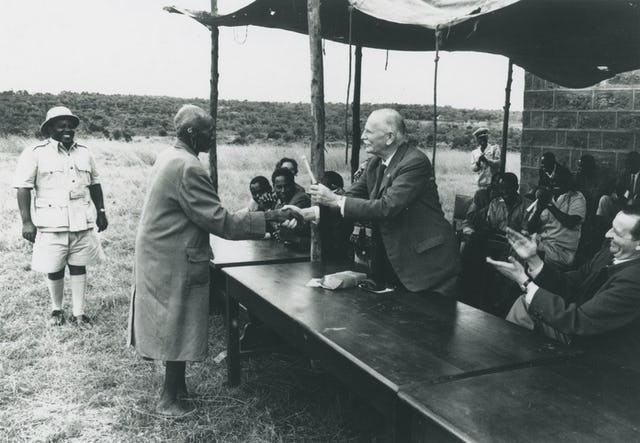 St. Barbe, facing left, shakes hands with a friend at a reunion of the original founders of Men of the Trees in the 1950s. Men of the Trees was founded in 1924 after St. Barbe's work in Kenya.