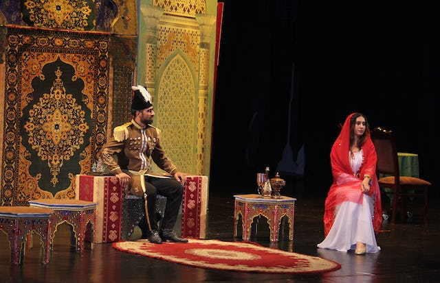 "This scene from the play Daughter of the Sun depicts when Nasiri'd-Din Shah, the king of Persia, met with Tahirih, offering to marry her if she recanted her faith. Tahirih turned down the offer with poetry: ""Kingdom, wealth, and power for thee / Beggary, exile, and loss for me / If the former be good, it's thine / If the latter is hard, it's mine."""