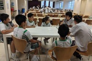 Deux lycéens aidant un groupe de collégiens dans le cadre du programme d'habilitation morale de l'école.