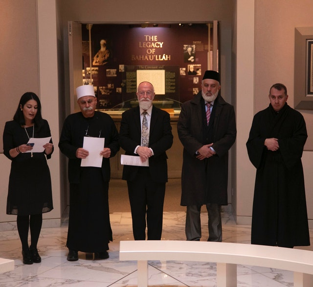 (From left) Carmel Irandoust, deputy secretary-general of the Baha'i International Community, reads a prayer as Sheikh Jaber Mansour, Rabbi David Metzger, Emir Muhammad Sharif Odeh, and Father Yousef Yakoub listen.