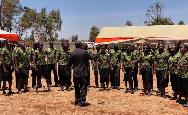 La chorale de la communauté hôte lwanda, chante lors de la cérémonie pour marquer le début de la construction du temple Matunda Soy.