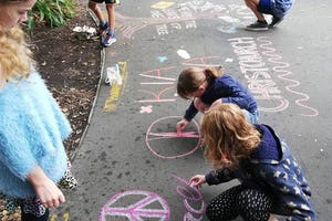 A group of young people draw chalk art on a sidewalk in Christchurch. A group of families involved in Baha'i community building activities in a neighborhood began the street art activity to inspire hope following the 15 March terror attacks.