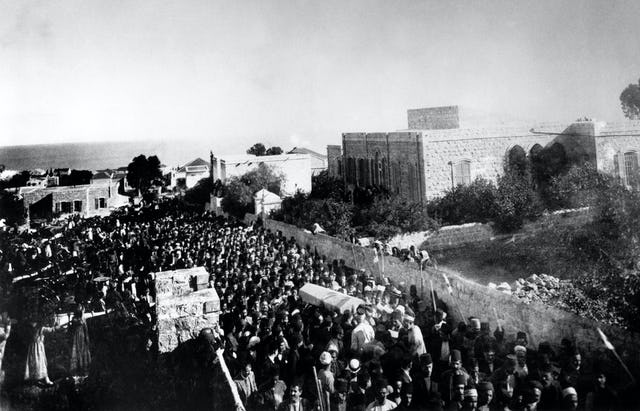 More than 10,000 people attended 'Abdu'l-Baha's funeral, held on 29 November 1921, the day after His passing. This photo shows the start of the funeral procession outside of 'Abdu'l-Baha's home in Haifa at the bottom of Mount Carmel. His remains were temporarily laid to rest in a vault inside the Shrine of the Bab. The House of Justice announced the construction of a permanent Shrine of 'Abdu'l-Baha.