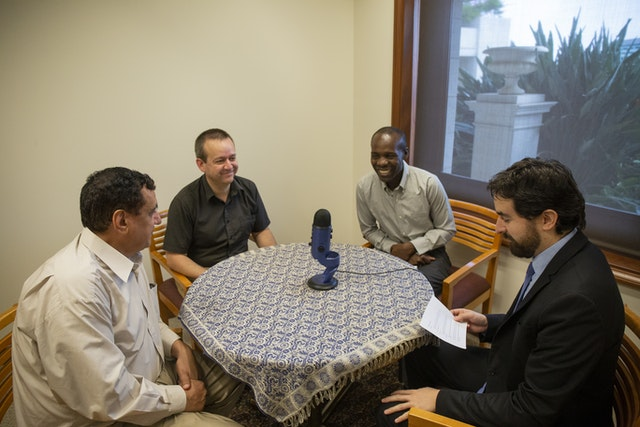(Clockwise from left) M. A. Ghanbari of India, Eduardo Rioseco of Chile, Santos Odhiambo of Uganda, and Felipe Duhart of Chile speak in the latest Baha'i World News Service podcast episode about the evolution of Baha'i Houses of Worship.