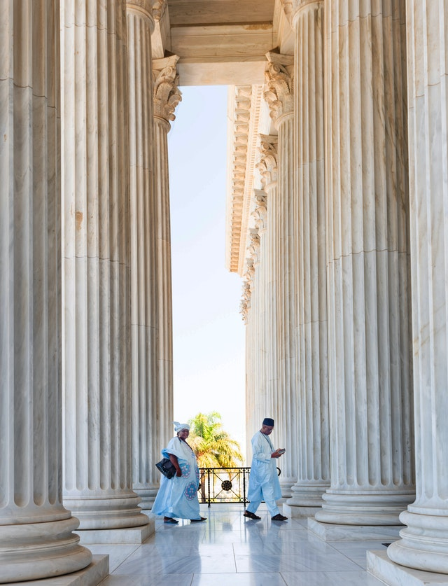 Two pilgrims enter the Seat of the Universal House of Justice.
