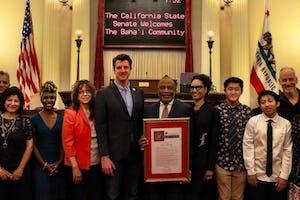 Miembros de las comunidades bahá'ís de California posan para una foto con el senador Henry Stern (quinto desde la izquierda).