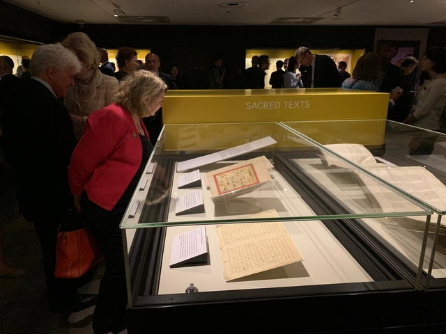 À la soirée inaugurale de l'exposition dans la salle des trésors de la British Library, des visiteurs examinent les manuscrits originaux du Báb et de Bahá'u'lláh.