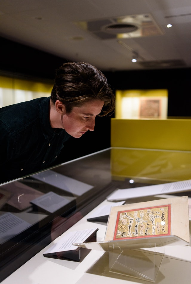 A visitor to the British Library views original Baha'i texts on display as part of an exhibition of the sacred writings of several religious traditions. (Credit: Richard Eaton, British Library Board)
