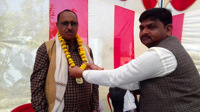 Ashok Kumar Rajput, a village chief, adorns his fellow pradhan with a garland in a sign of welcome. Mr. Rajput worked closely with the Baha'i community to gather his colleagues to draw on the insights and experience arising from initiatives in their communities inspired by Baha'u'llah's teachings.