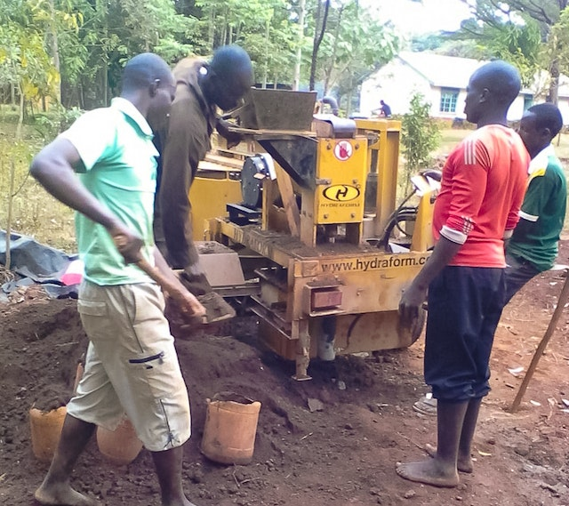 The project to build an educational facility in Namawanga used a hydraulic machine that presses bricks made mostly of soil from the site. The machine produces interlocking bricks that are simple to assemble with no need for mortar.