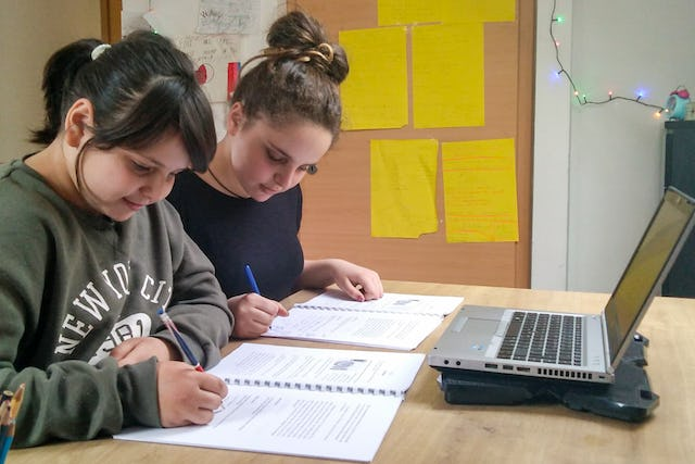 Two sisters in Bašelj, Slovenia, who are part of a group of youth participating in Baha'i educational programs that develop capacities for service to society. They now connect online with the other members of their group from their home, in accordance with public health guidelines.