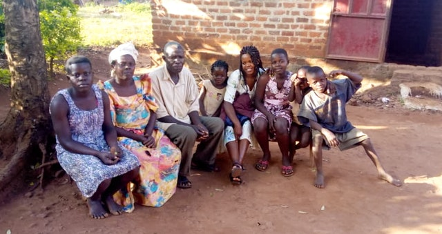 Image features residents of the same household. A family gathered outside their home in Kiyunga, Uganda, listen to a broadcast presented by the Baha'is of the village. Although public gatherings, including those for worship, are suspended across the country, residents of the same home are encouraged to continue praying among themselves.