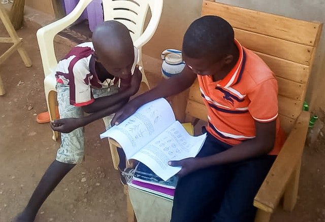 "Students of a community school in Bangui, Central African Republic, study at home. ""The approach of decentralized schools is opening unexpected doors,"" says Mr. Mokolé. ""This has given us the possibility to help parents increase their understanding of educational principles and skills, which is precious because the home is the primary locale for the education of children."""