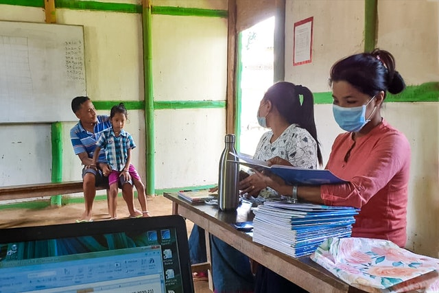 Teachers at a community school in Langathel, Manipur, India, distribute schoolwork to parents to carry out with their children at home as a precautionary measure during the health crisis.