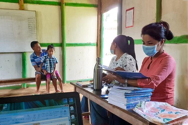 Par mesure de précaution pendant la crise sanitaire, les enseignants d'une école communautaire de Langathel, Manipur, en Inde, distribuent des travaux scolaires aux parents pour qu'ils les fassent avec leurs enfants à la maison.