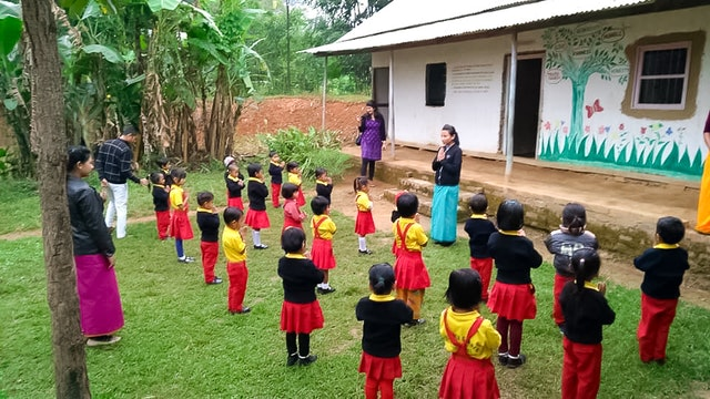 Photograph taken before the current health crisis. Teachers and children at a community school in Langathel, Manipur, India. Decades of grassroots educational efforts of Baha'is in several countries have led to the emergence of community schools, drawing on the capacity and resources that exist in a local area.