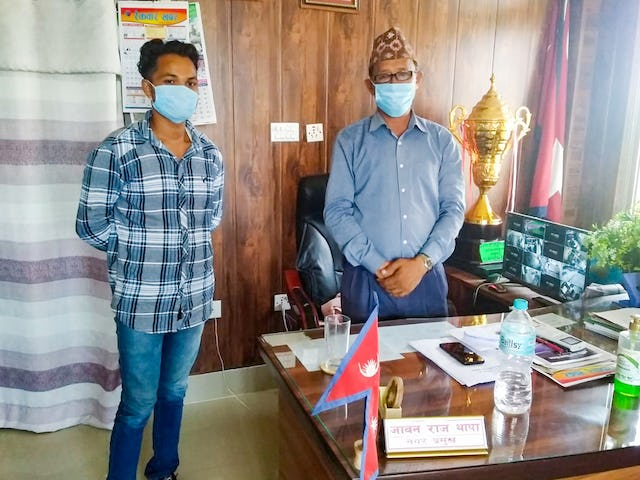 A member of the Baha'i Local Spiritual Assembly of Motibasti, Nepal, meets with the mayor to deliver a letter describing an irrigation challenge faced by some village members.