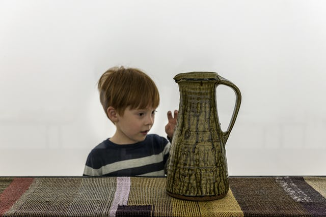 A young visitor examines a Bernard Leach jug at the installation, Kai Althoff goes with Bernard Leach at the Whitechapel Gallery, London, 7 October 2020 – 10 January 2021. Photo: Polly Eltes