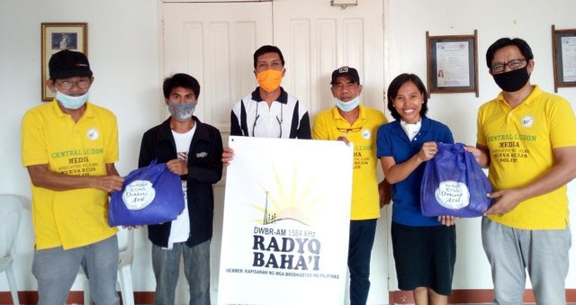 Staff of Radyo Bahá'í in the Philippines collaborate with members of the Central Luzon Media Association to distribute relief in the region.