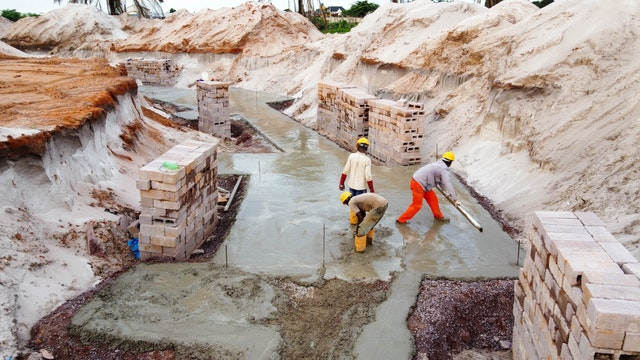 A process known as concrete blinding creates a smooth surface to work on. Masonry blocks are then used to create formwork for the reinforced concrete foundations.