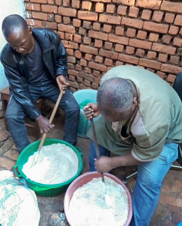 A health educator is seen here teaching community members to make a nutritional flour mix.
