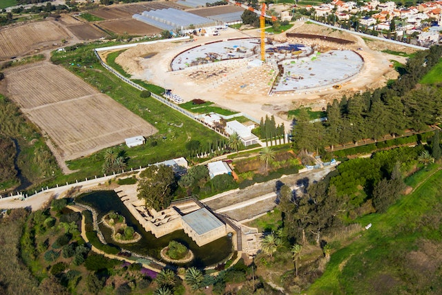 An aerial view shows recent progress in the construction work for the Shrine of 'Abdu'l-Bahá. The site for the Shrine is located near the Riḍván Garden, which is visible in the foreground.