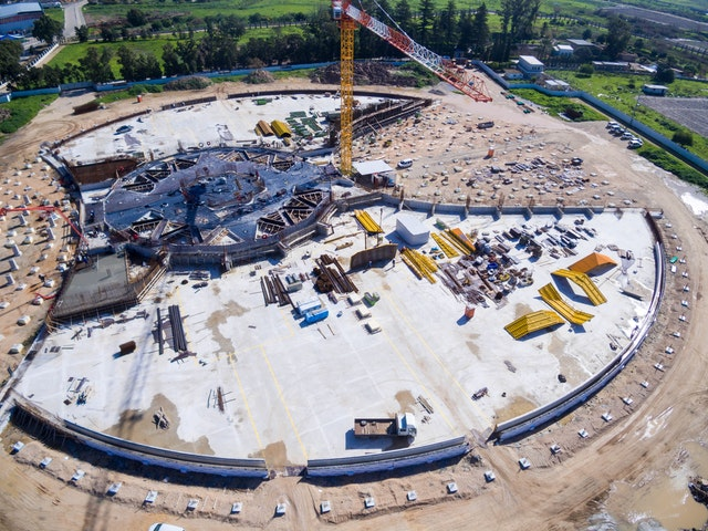 In this aerial view of the construction site from the west, the completed concrete bases for the two garden berms reveal the outline of the Shrine. Visible in the middle of the site is the formwork where concrete will be poured for the floor of the central plaza.