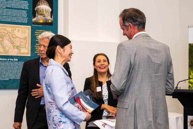 In-person gatherings held according to safety measures required by the government. Jing Lee (left), the assistant minister to the premier of the state of South Australia, speaks with representatives of the Bahá'í community at a gathering in Adelaide, South Australia.