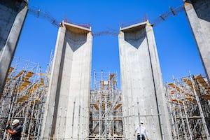 En plus des piliers, le premier ensemble de murs plissés est terminé et les préparatifs commencent pour un treillis qui surplombera la place.