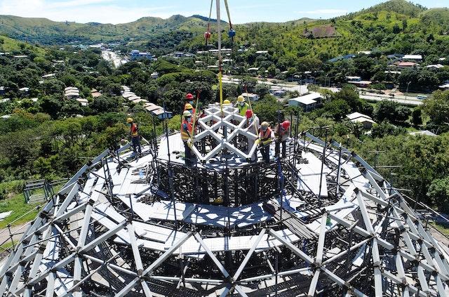Los trabajadores de la construcción acomodan el primero de los nueve elementos prefabricados de la cúpula.