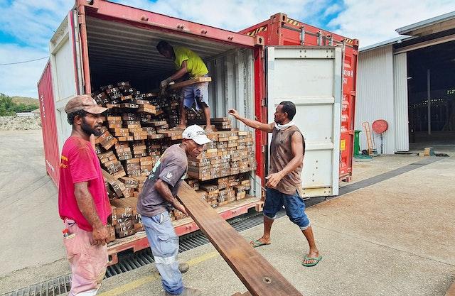 Los obreros descargan un cargamento de madera reciclada que revestirá la parte inferior de las marquesinas de las entradas y el interior de los muros del edificio central.